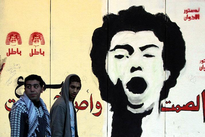 Anti-Morsi protesters walk in front of a mural of activist Gaber Salah