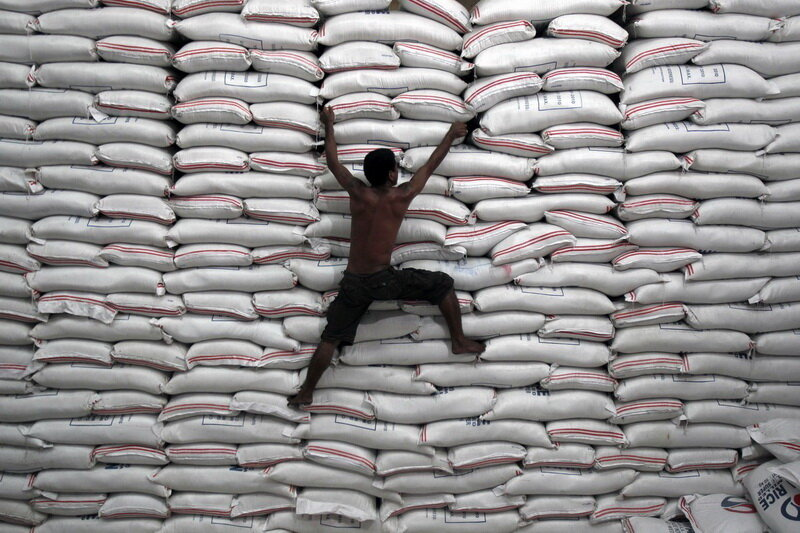 A worker climbs on a pile of rice stock inside a warehouse of the government National Food Authority (NFA) in Bicutan