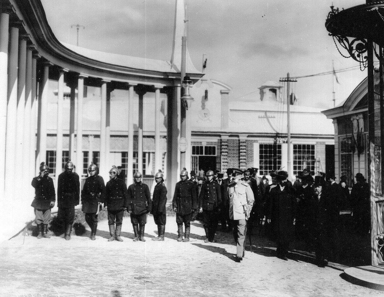 53. Публика, выходящая из выставочного павильона, проходит мимо строя пожарных, несущих дежурство на выставке