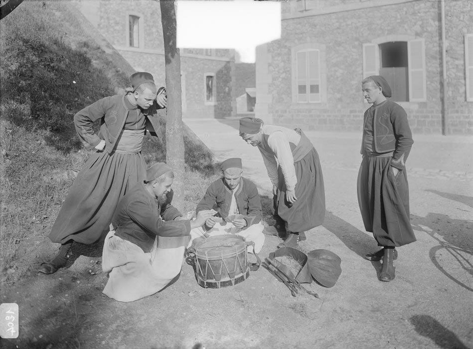 Des zouaves jouent une partie de cartes sur un tambour.