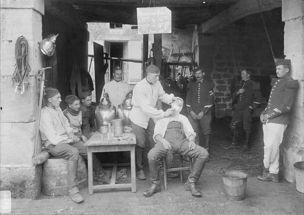 Au 11e regiment de cuirassiers, le perruquier rase un soldat sous le regard attentif de ses camarades.