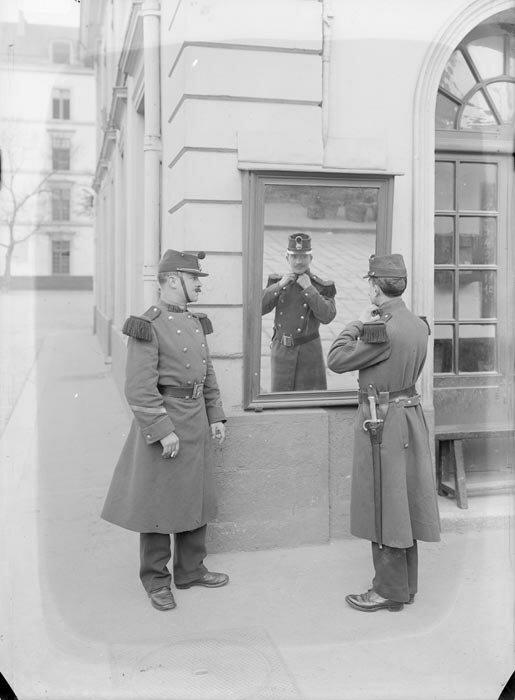 Un soldat du 89e regiment d'infanterie en tenue de sortie d'hiver ajuste le col de son uniforme devant la glace du poste sous les yeux attentifs d'un camarade.