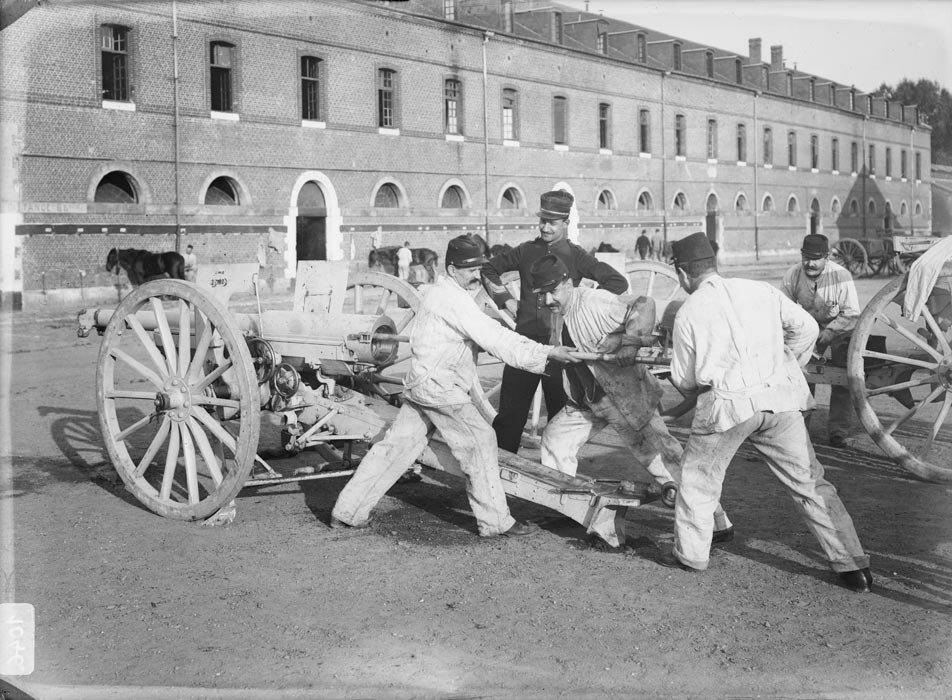 Les servants en tenue de corvee nettoient l'ame du canon de 75 mm a l'aide d'un ecouvillon sous la surveillance de l'instructeur d'artillerie.