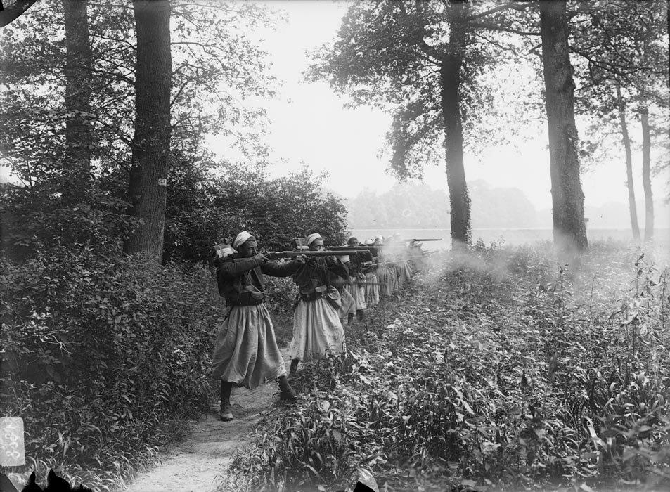 Une colonne de zouaves en tenue de manœuvre s'exerce au tir avec un fusil Berthier modele 1907.