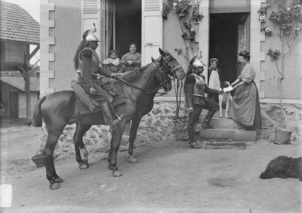 Deux cavaliers du regiment de cuirassiers en tenue de mobilisation apportent le billet de logement chez des particuliers.