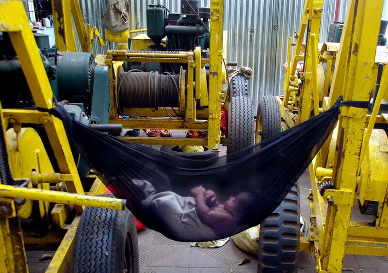 A child of an Indian labourer, lies in a hammock tied to cranes in Bombay.