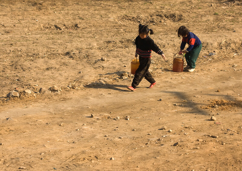 KIDS BRINGING BACK WATER FROM TANK IN THE COUNTRYSIDE, NORTH KOREA