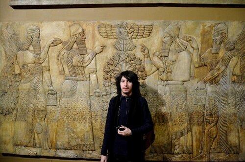 АРИЙ РАдаСлав в Московском Музее изобразительного искуства пред Месопотамским рельефом где стоят цари с древними оконтами - жерельями на которых присутствуют  Знаки РАтаи