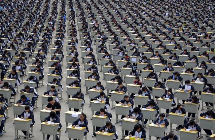 Студенты сдают экзамен на детской площадке средней школы под открытым небом в Yichuan, провинция Шэн