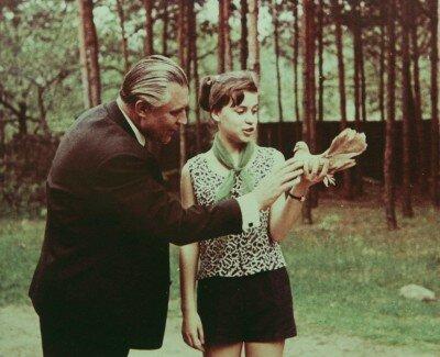 Владимир Васильевич Щербицкий  учит Ольгу правильно держать в руках голубя