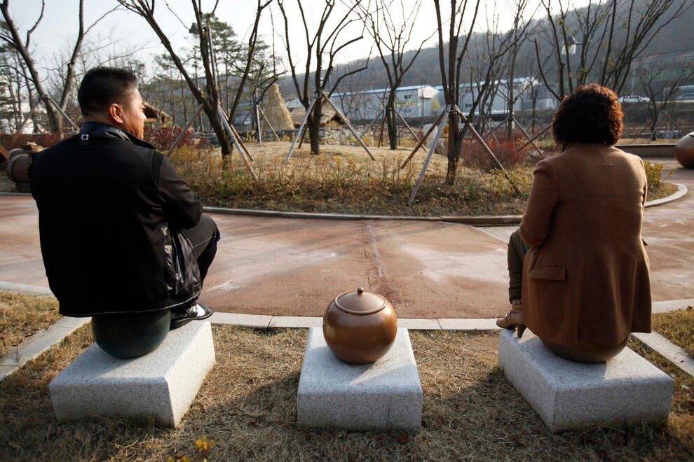 Посетители парка сидят на горшках.