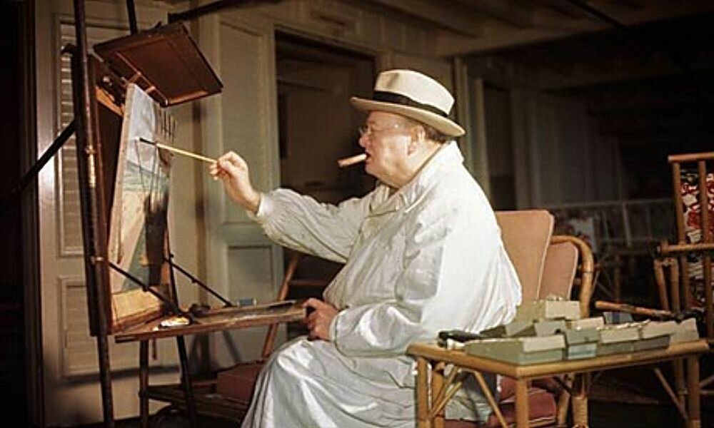 Winston Churchill painting at his easel February, cigar clamped firmly in his mouth. Photograph: Bettmann/Corbis