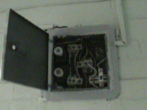 Фото 1. Этажный щит с плавкими предохранителями (пробками) на вводах в квартиры. Одна из пробок (в правом верхнем углу щита) выпала из патрона (основания).