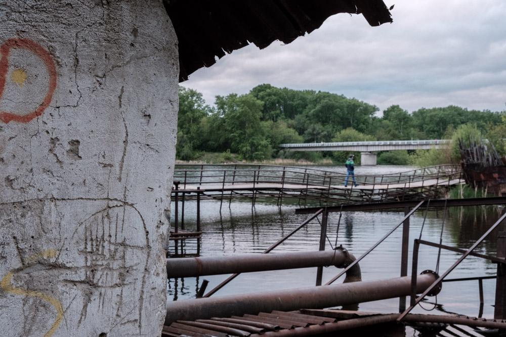 мужчина идет по железному мосту