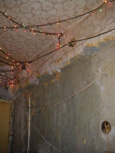 Фото 16. В коридоре вместо традиционного светильника установлена гирлянда. Стационарный выключатель отсутствует. Распределительная коробка открыта.