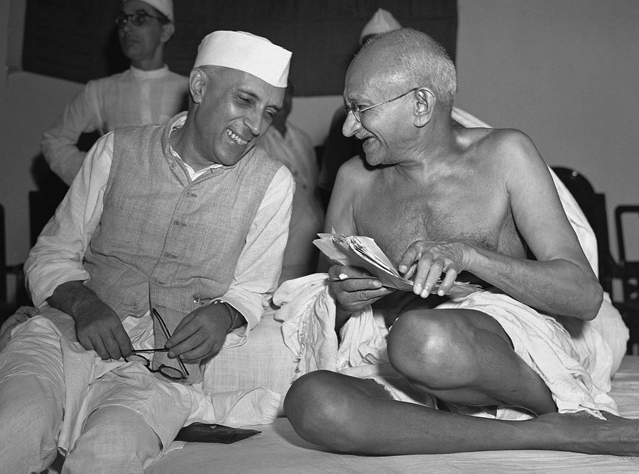 Bespectacled Mahatma Gandhi laughs with Jawaharlal Nehru, at the All-India Congress committee meetin