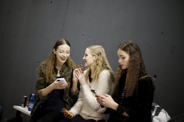 Models use their phones backstage of the Aquilano Rimondi Autumn/Winter 2016 woman collection during