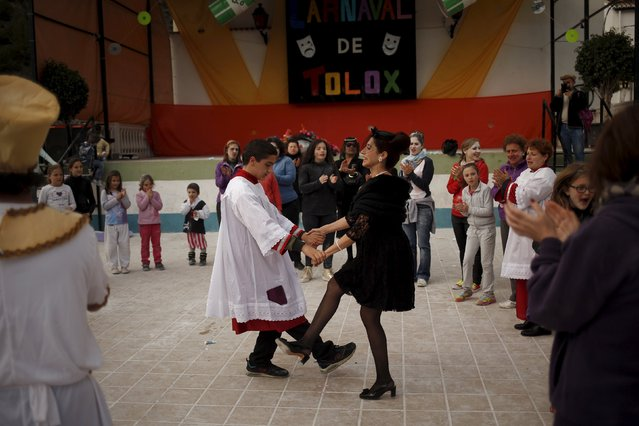 A boy dressed up as an altar boy and a woman dressed up as a widow perform a traditional dance as th