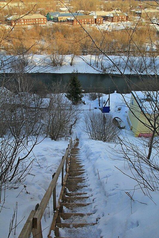 Узкая деревянная лестница на высоком крутом склоне берега Вятки, ведущая к Ежовскому родниковому комплексу и в Вересники