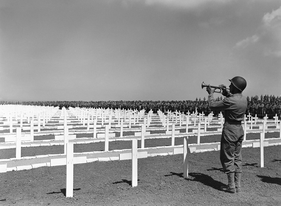 Corporal Louis Peter Kontas of Malden, Massachusetts, sounds taps at a Marine cemetery on Okinawa, J