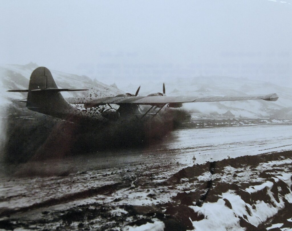 Consolidated PBY Catalina raises, a veritable cloud of mud as it comes to rest on the muddy landing field at Amchitka, in the Aleutian Islands, June 23, 1943