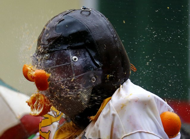 A participant is hit by an orange during an annual carnival battle in the northern Italian town of I