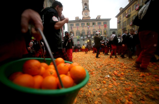 A member of a rival team carries oranges during an annual carnival battle in the northern Italian to