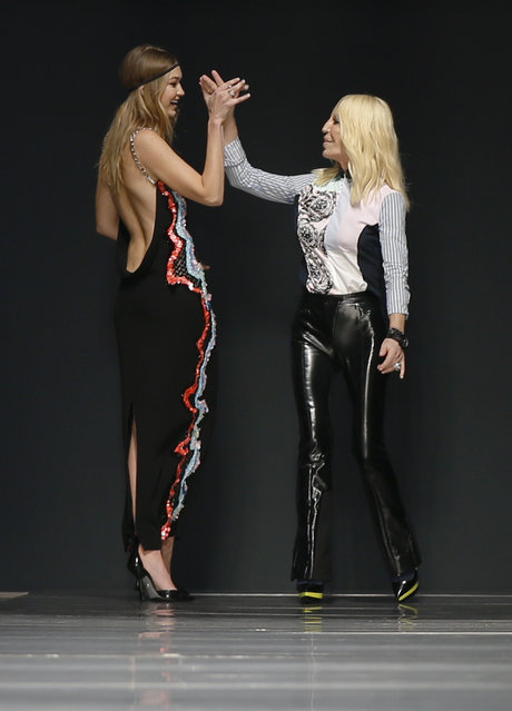 Fashion designer Donatella Versace, right, salutes model Gigi Hadid at the end of the Versace women&