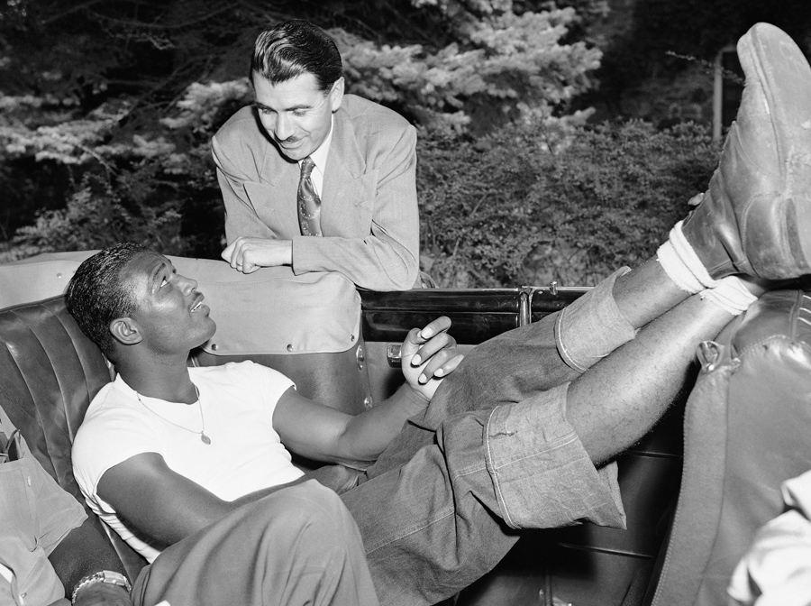 Harold Mayes, (standing) sports editor for Empire News, chats with Sugar Ray Robinson, boxer, at a t