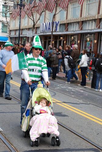 Мужчина в бело-голубой майке и шапке с ребенком в коляске