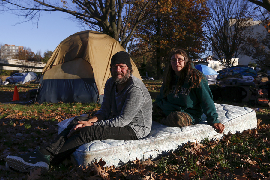 Clyde Burgit and his wife Helen, who had been at this camp for two weeks, sit on a mattress near the