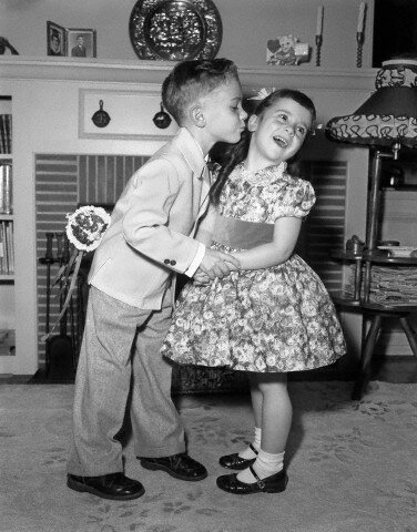 J1950s little boy in suit and tie trying to kiss little girl in party dress