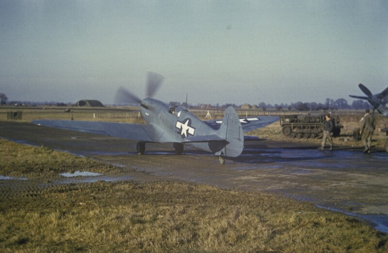 Mark XI Spitfire (sn MB950) 'Upstairs Maid', of the 14th Photographic Squadron, 7th Photographic Reconnaissance Group taxies past a Cletrac at Mount Farm