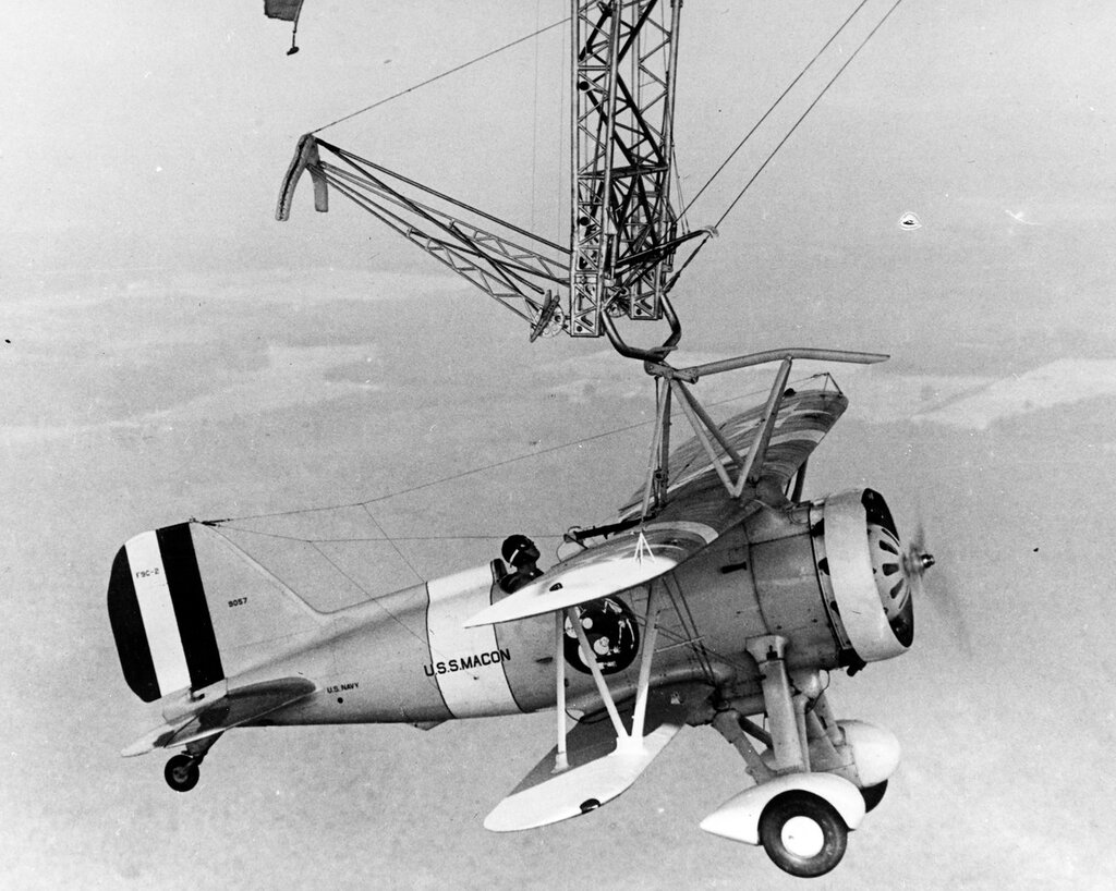 Curtiss F9C-2 Sparrowhawk fighter #9057, piloted by Lieutenant D. Ward Harrigan, USN. Hanging from the trapeze of USS Macon (ZRS-5) during flight operations in 1933