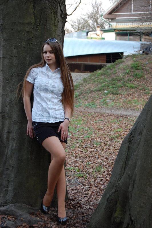 Красотка в белой блузке возле дерева