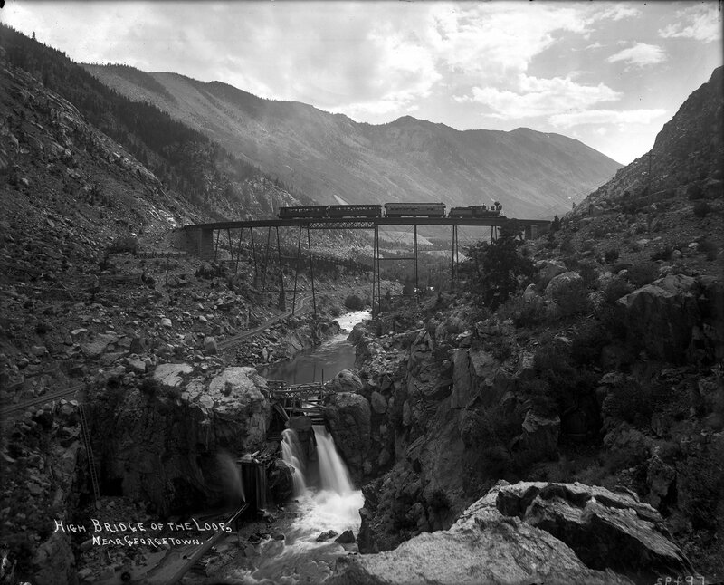A Union Pacific, Denver & Gulf passenger train crosses a trestle over a canyon and Clear Creek near Georgetown, Colorado, 1895