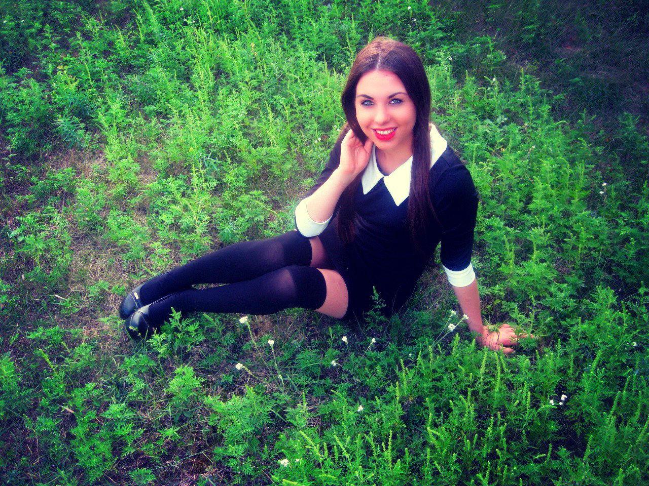 Длинноволосая шатенка на траве в чулках