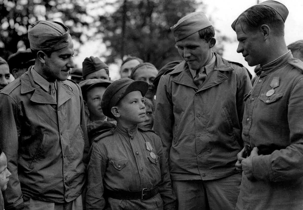 Сержант С. Вайншенкер и техник-сержант Вильям Топпс с сыном полка 169 авиабазы особого назначения. Имя неизвестно, возраст — 10 лет, служил помощником техника по вооружению. Аэродром Полтава. 1944 г.