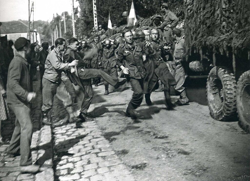 A German POW is kicked by a French civilian, 1944