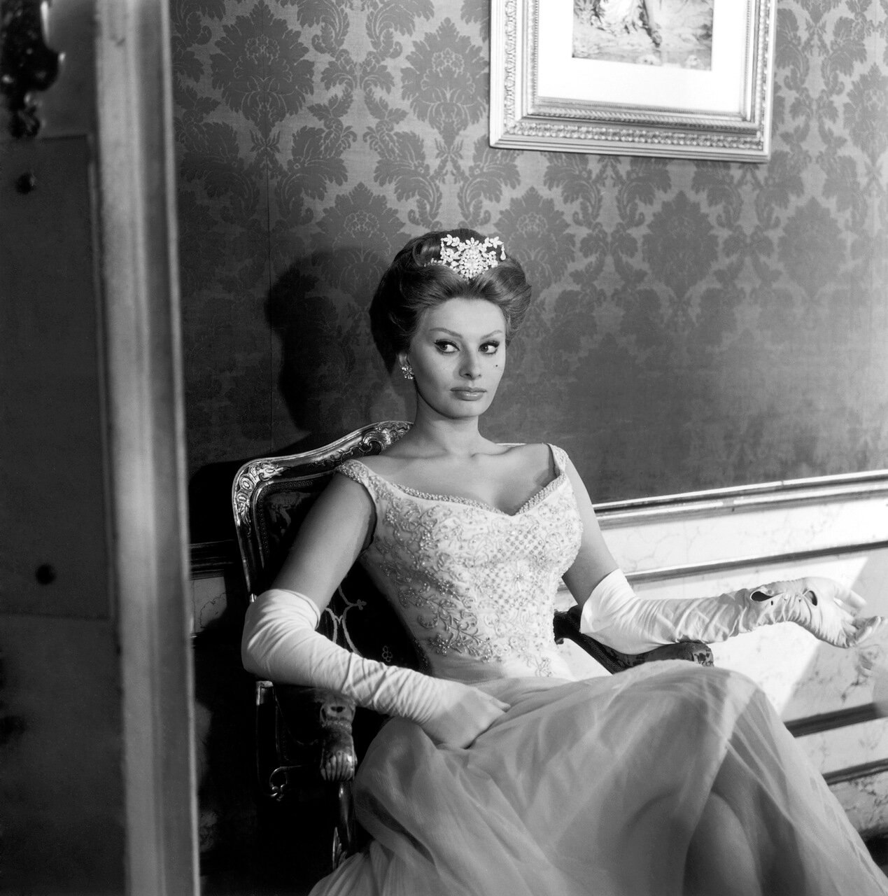 1960: Italian actor Sophia Loren wears a ball gown, long white gloves, and a tiara while sitting in an armchair on the set of director Michael Curtiz's film, 'A Breath of Scandal'.