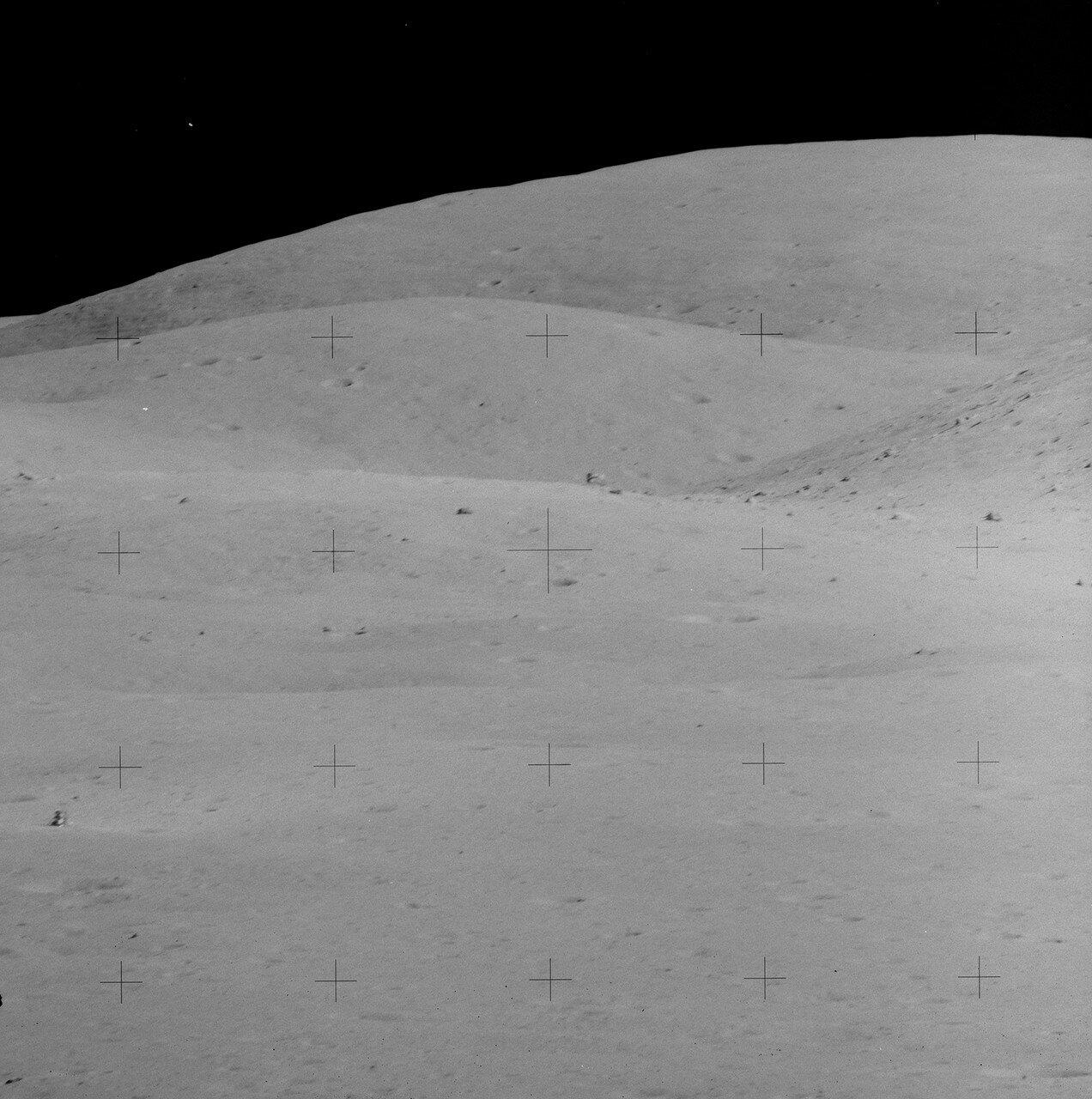 До первой геологической остановки (Station 4) во второй поездке астронавты добрались примерно за 38 минут На снимке: Лунный модуль «Орион» вдали (слева внизу). Видна скала House Rock, огромный валун на краю кратера Северный Луч