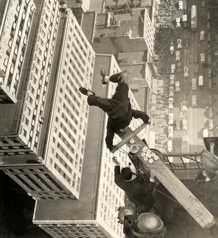 Man balancing on a board on top of a skyscraper, 1939.