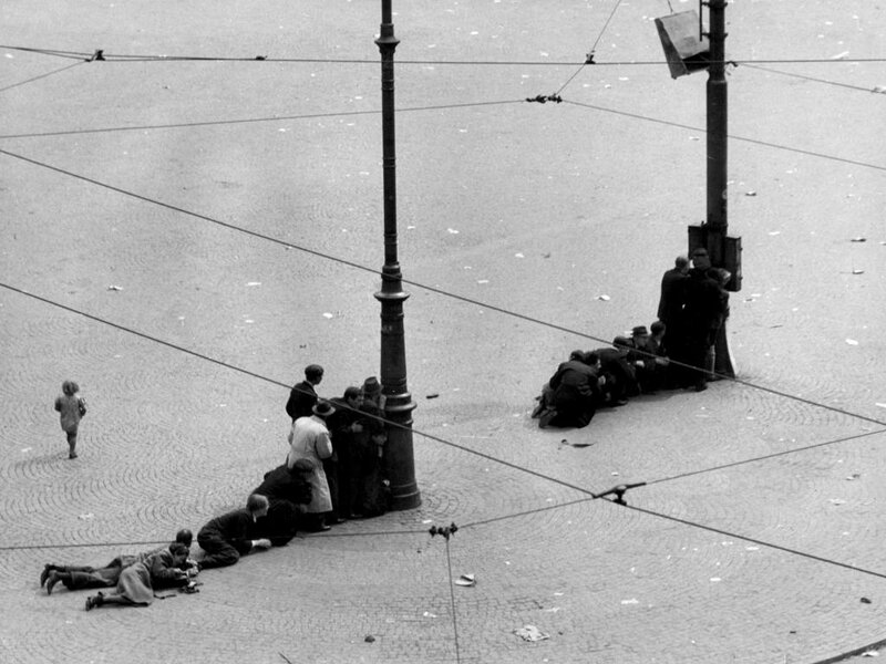 People seeking shelter behind lamp-posts at Dam square Amsterdam after German troops opened fire at the celebrating masses (22 killed, 120 injured), 7 May 1945.