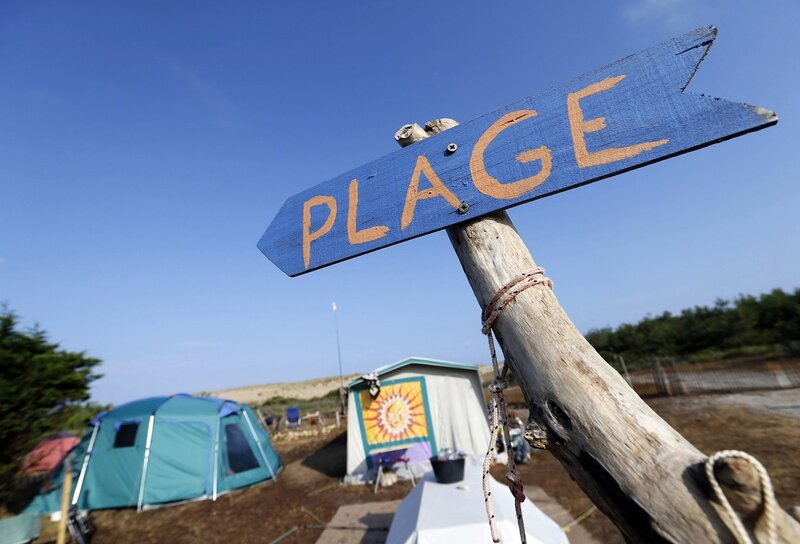 A sign near tents indicates the direction to the beach at the Centre Helio-Marin naturist campsite on the Atlantic coast in Montalivet