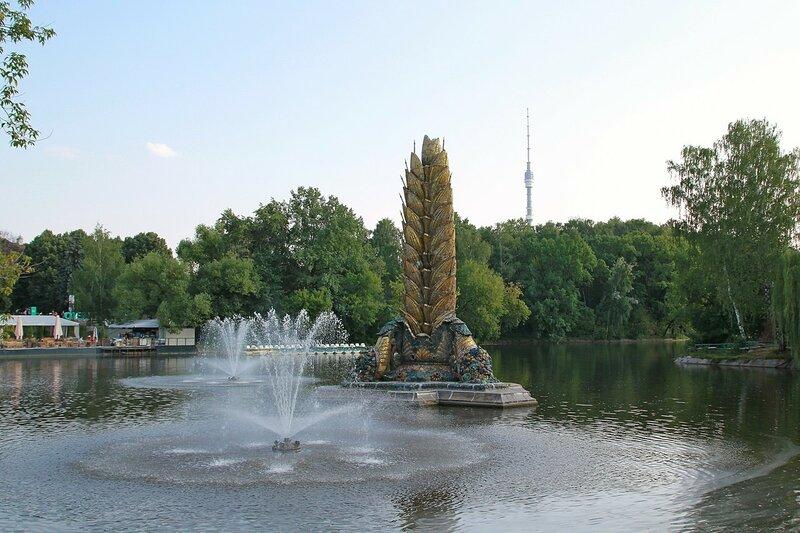 Фонтан «Колос» в центре верхнего пруда ВДНХ рядом с бывшим рестораном «Золотой колос» и шпиль Останкинской телебашни на фоне за деревьями