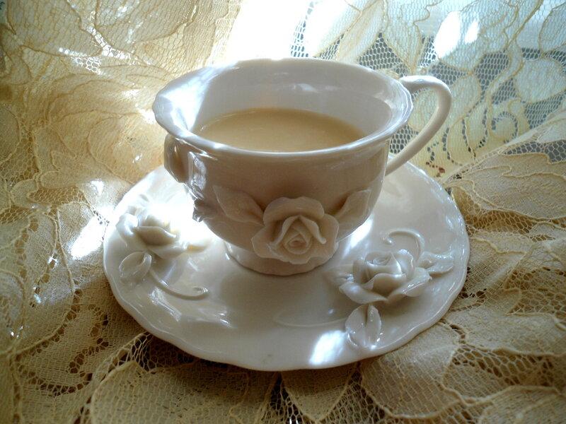 Топлёное молоко в чашечке цвета топлёногно молока на фоне занавески цвета топлёного молока.
