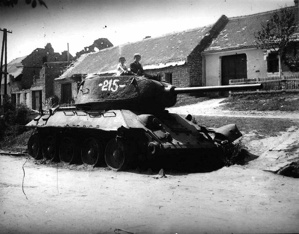 Подбитый советский танк Т-34-85 и сидящие на нем дети. Май 1945 года.