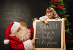 Santa Claus with child sitting near chalkboard with wish list and checking it