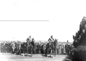 Император Николай II поздравляет юнкеров-артиллеристов, выстроившихся на военном поле, с производством их в офицеры.