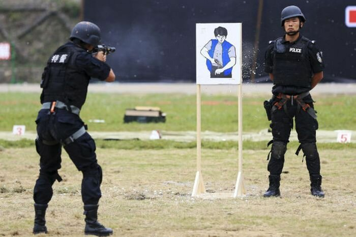 A policeman (R) from the Special Weapons and Tactics (SWAT) team stands next to a target as his teammate practises shooting with an assault rifle during an anti-terrorism drill in Foshan, Guangdong province September 29, 2013. Picture taken September 29,